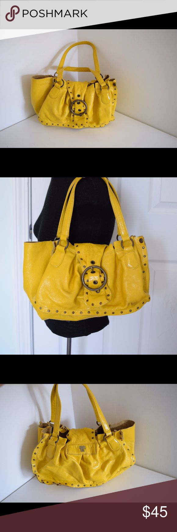"Ann Sui leather shoulder bag studded Anna Sui studded leather tote bag Measures 14"" x 9"" shoulder drop 9"". Snap closure. Leather in yellow (almost mustard color). Brass tone studs. Anna Sui logo Inside has ink marks (pic). Outside has one ink mark on back & one on front (pics). Beautiful bag. $200 new Anna Sui Bags Shoulder Bags"