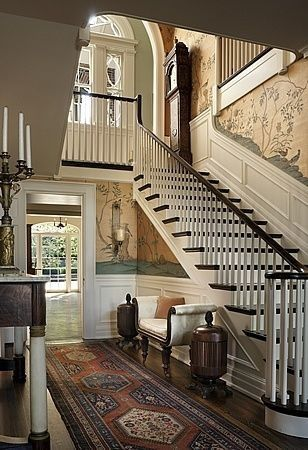 Beautiful entryway with artisan wallpaper and staircase, all trimmed in white with darker hardwood floors.