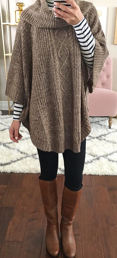 Heather brown cable knit poncho with a black striped turtleneck top, black leggings, brown riding boots