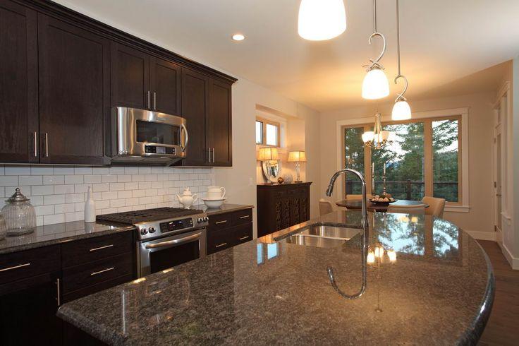 Preston Home (571) - dark cupboards, flate granite counters and white brick-style backsplash