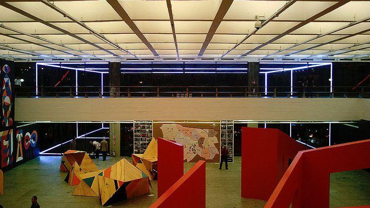 """Na obra """"Projeto de Expansão"""" o BijaRi propõe a ampliação perceptiva do espaço do museu para além de seus limites. Um desenho é feito com fitas de luz led aplicadas à parede de vidro, criando uma ilusão de espaço ampliado ao carregar a visão do público para além das paredes do museu. A intervenção se constitui num comentário sobre o território atual da arte e seu constante processo de expansão e contaminação para lém dos seus limites.Participou da exposição"""