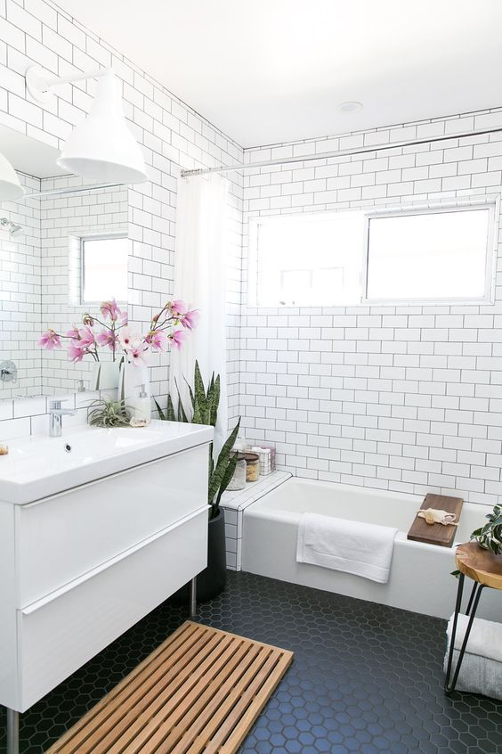 mid century modern bathroom with white subway tiles on the walls and black hexagon ones on the floor
