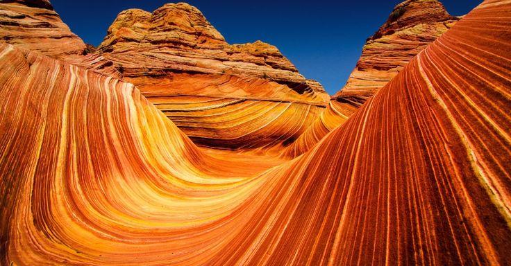 """The Wave, Arizona (EUA). Esta formação de rocha de arenito cujo desenho sinuoso lhe valeu o nome de """"onda"""" está localizada na área de Coyote Buttes, próximo à fronteira entre Arizona e Utah. A área atrai fotógrafos da natureza por sua beleza de rocha que parece ondular e que teria se formado como uma erosão em arenito navajo durante o período jurássico, há 190 milhões de anos. Segundo os fotógrafos, o melhor horário para fazer fotos é perto do meio-dia, mas para entrar nessa área preservada…"""
