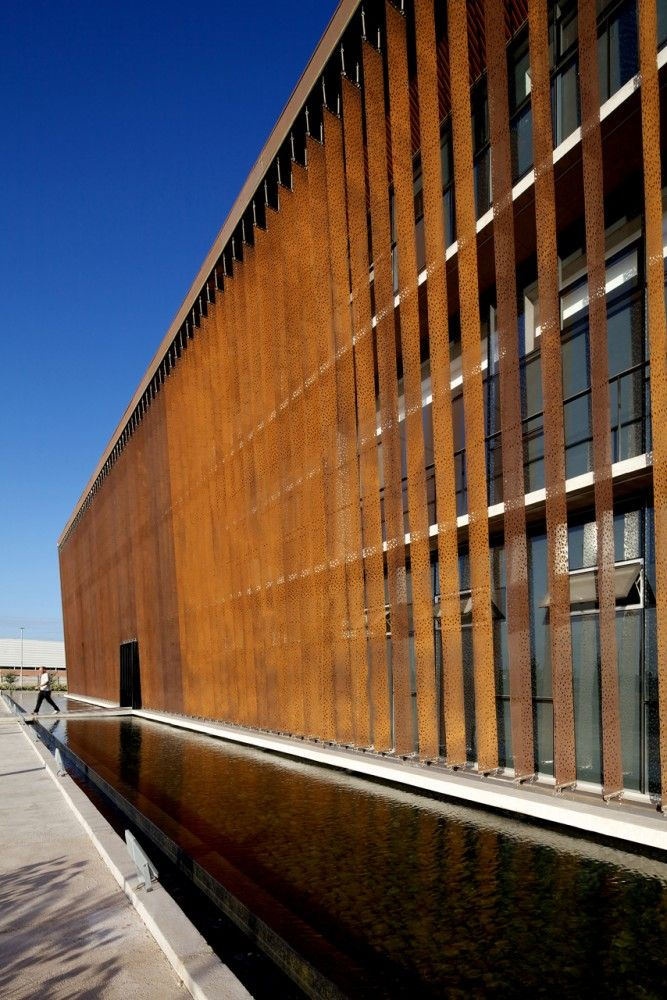 Corporate building for Ferretería O´Higgins in Santiago by Guillermo Hevia Architects.  Thin and perforated CORTEN steel fins protect the double envelope from solar insulation but leave clear views out.