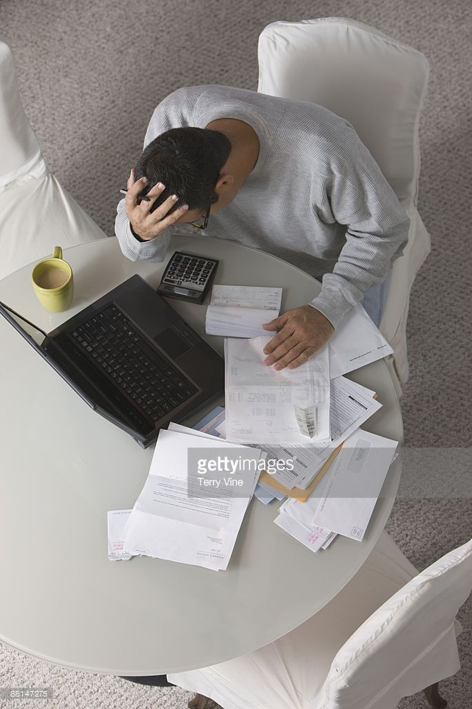 Overhead view of frustrated Hispanic man paying bills