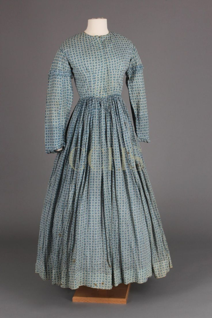 DRESS, 1852-1865 | Chester County Historical Society, blue printed cotton. This is an example of everyday dress. This dress is utilitarian but still embellished. Ruffles detail the sleeve cap and sleeve opening but the wide pagoda sleeves could be rolled up for more laborious activities.