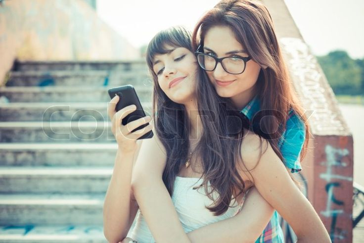 Stock image of 'beautiful hipster young women sisters friends using smartphone  in the city'