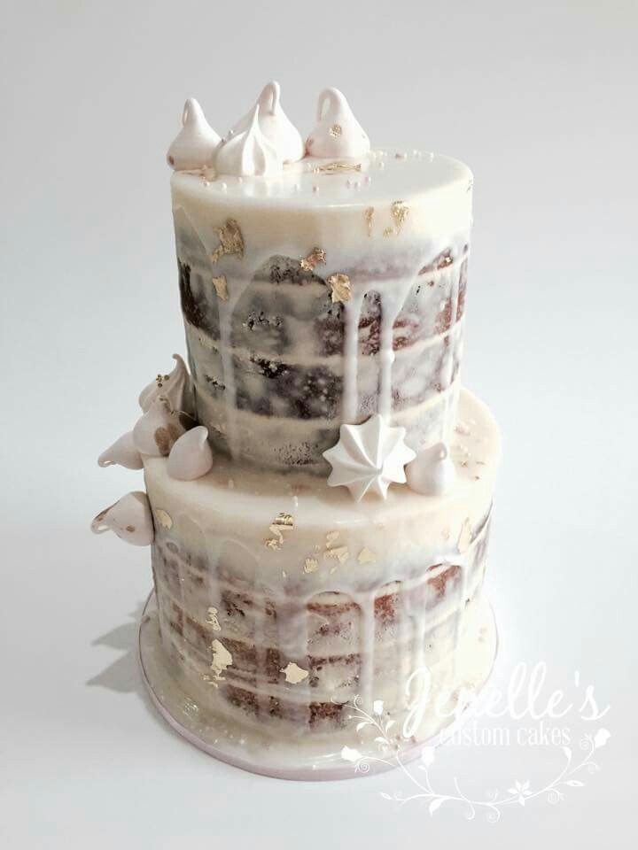 Semi naked cake in White chocolate mud cake and cookies and cream mud cake, filled and lightly coated with white chocolate ganache. Drizzled with royal icing, flecked with edible gold leaf and topped with sweet meringue