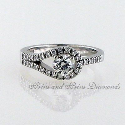 Centre stone is a 0.506ct H/VS2 Round brilliant cut diamond with 28 = 0.19ct round diamonds set in a tube halo 18k white gold band