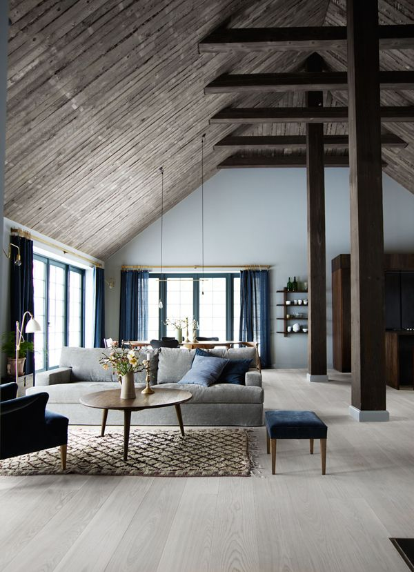 Stunning Scandinavian living space with high wood clad ceilings and dark blue curtains.