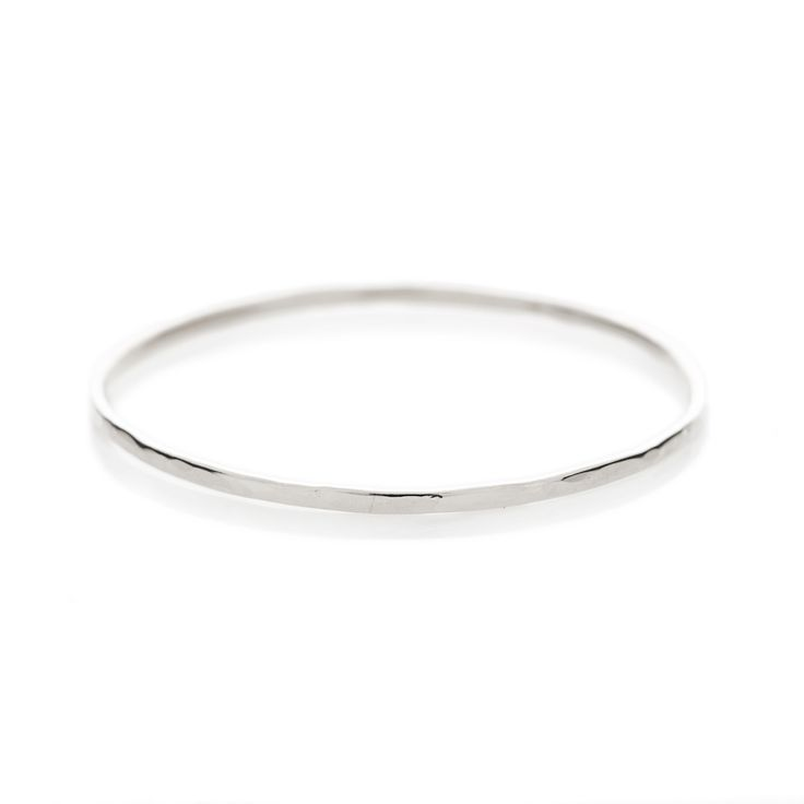 A thin sterling silver bangle with hammed texture.