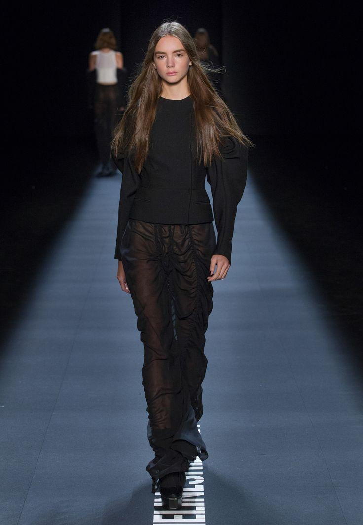 LOOK 39. Black wool double-breasted jacket with draped sleeve. Black silk georgette long draped skirt.