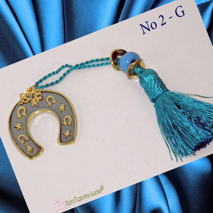 Μεταλλικό πέταλο σε χρυσό χρώμα με σιέλ σμάλτο, δεμένο σε γούρι για το 2018 με μία γαλάζια φούντα διακοσμημένη με δύο μεταλλικές ροδέλες και μία γαλάζια κεραμική χάντρα. Ιδανικό ως δώρο για το νέο έτος. Ελληνικό χειροποίητο προϊόν. Good luck charm for 2018. A metal horseshoe with light blue enamel on a light blue tassel decorated with metal grommets and a light blue ceramic bead. Perfect gift for a happy new year. Made in Greece.