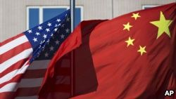 FILE - U.S. flag and China's flag flutter in winds at a hotel in Beijing. -  The report did note improvements in China's long-reviled one-child policy, which was relaxed last year, and Beijing's decision, in theory, to eliminate its infamous re-education through labor camps.