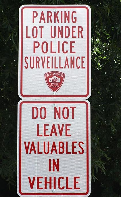 """Parking Lot Under Police Surveillance. Do Not Leave Valuables In Vehicle."" - Another funny sign to perk up your Wednesday!"