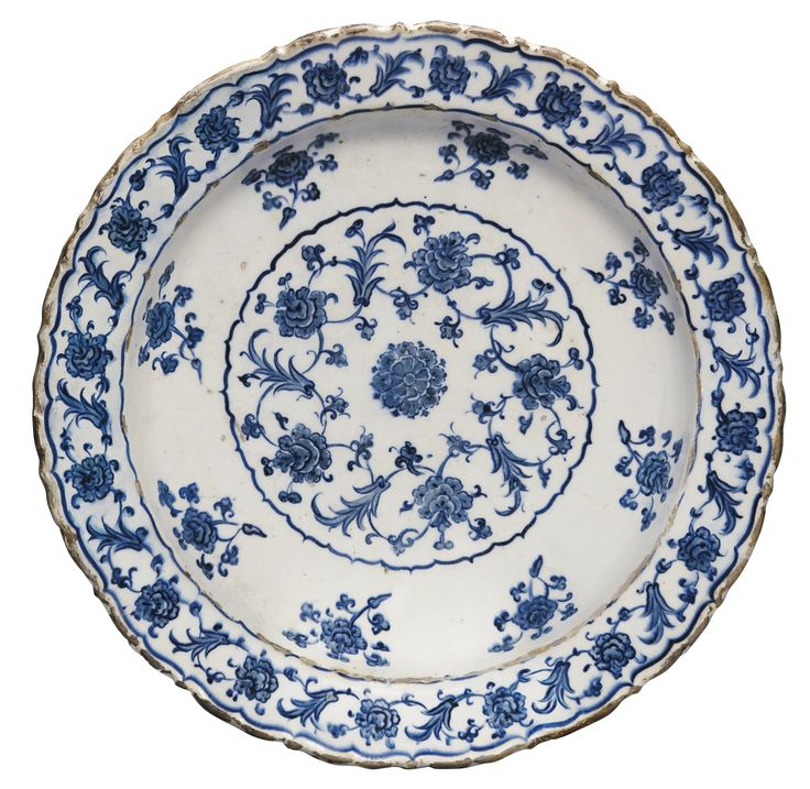 A RARE IZNIK BLUE AND WHITE CHINOISERIE TAZZA, TURKEY, CIRCA 1560-70 of deep rounded form with sloping bracketed rim, resting on a raised everted foot, decorated in underglaze cobalt blue and grey-blue with a central rosette encircled by lotus palmettes entwined with a wheatsheaf motif, the cavetto with lotus stems to the interior and exterior, the rim and foot repeating the design around the central medallion