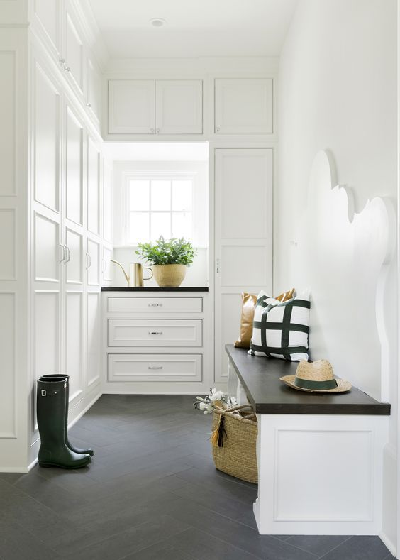 white mudroom with dark floors (love the back of the bench)