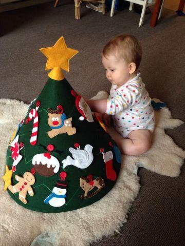 Árvore de Natal lúdica e segura para bebês. Tudo foi feito com feltro: desde o cone para garantir o formato da árvore até os enfeites, que são fofos e estão presos por um botão costurado.