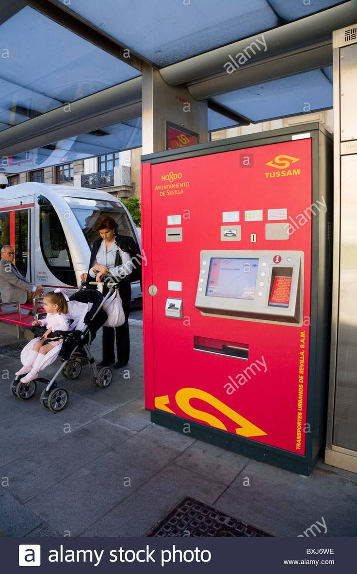 Download this stock image: Mother, baby in param, modern vending machine for tram tickets passengers / trams passenger ticket / at tram stop Seville. Spain - BXJ6WE from Alamy's library of millions of high resolution stock photos, illustrations and vectors.