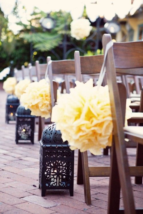 Lighted lanterns also make great aisle decor. If the lanterns are smaller, you can hang them directly on the chairs. If they're larger, sit them by the first seat of every row to light the way down the aisle!