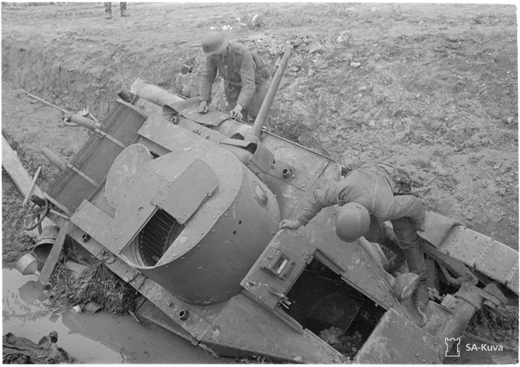 Finnish soldiers examine a disabled Soviet tank, 27 August 1941. Note unfired shells stored in the turret.