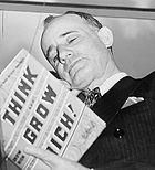 Napoleon Hill holding his book Think and Grow Rich