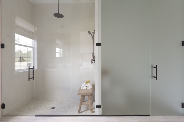 a floor to ceiling glass shower door opens the bathroom to ample light and usable space ample shower lighting