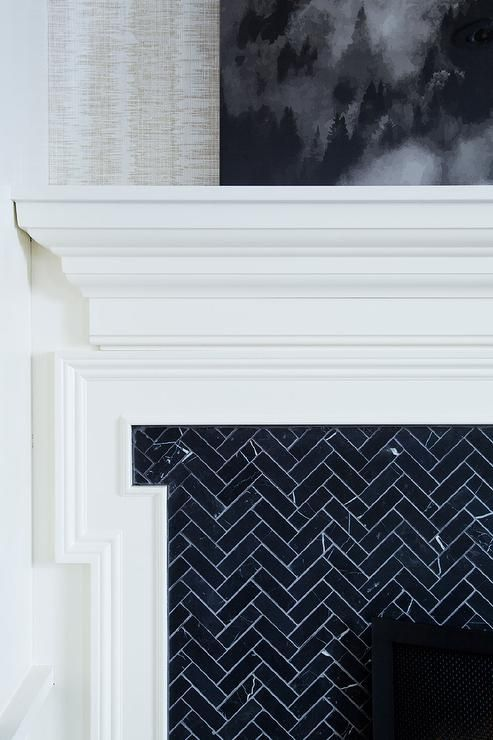 Chic white fireplace mantle with Greek key trim is fitted with a black herringbone tile surround.