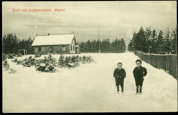 MAGNOR i Eidskog kommune i Hedmark fylke. Parti fra Ungdomslokalet. Med to små gutter i veien. Fot. Larsen-Normans Kortforlag. Br. 1911