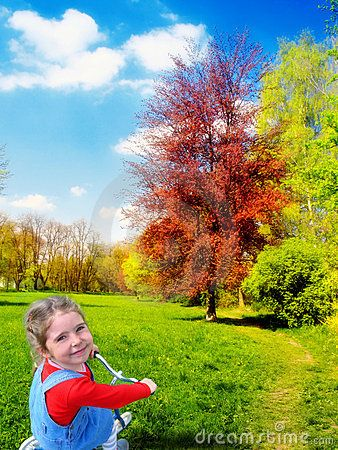 Happy smiling girl on tricycle in sunny landscape