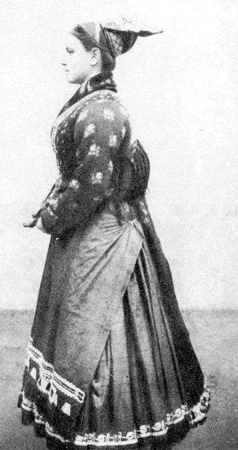 """Fiatalasszony 1880-ból, """"féketőben"""". Felső testén bélelt rékli, szoknyája fölött bő kötény, azelőtt pedig hímzett surc"""