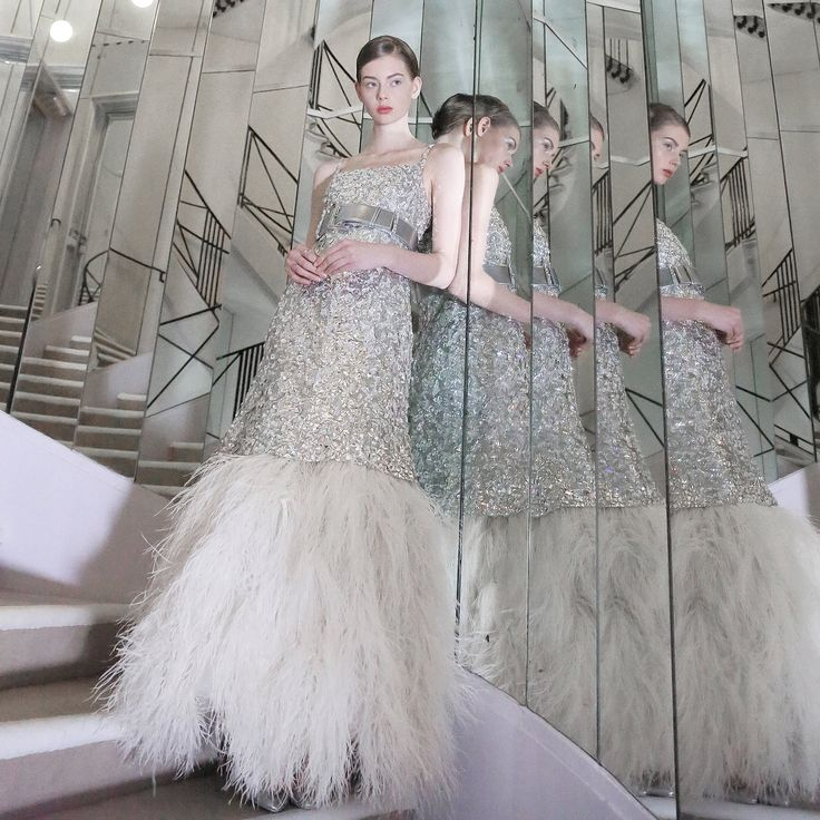 Chanel's mirrored and feather-trimmed spring 2017 gown is similar to the one from the eighties because of the reflective detailing and feathers found at the bottom. This dress is also different because it has straps and is floor length instead of short. These details as well as the broken mirrors make it overall more glamorous than the older dress. Lexis Gervais. 4/6/17.
