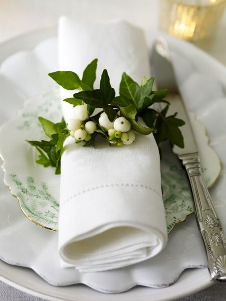 Tableware with scalloped edges  subtle green pattern. White linen napkin tied with ivy  berries / Sarah Kaye Representation: Polly Wreford
