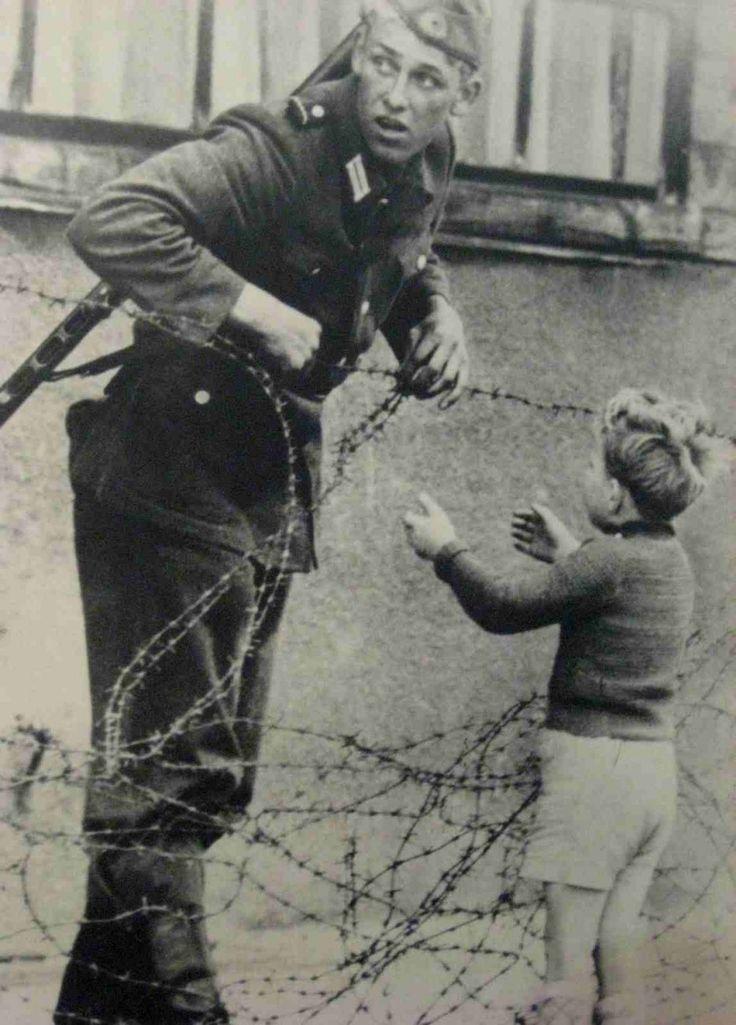 """Um soldado da Alemanha Oriental ignora ordens para não deixar ninguém passar e ajuda um menino, que foi encontrado no lado oposto de sua família, a atravessar o """"Muro de Berlim"""" recém-construído. [Guerra Fria, 1961]"""