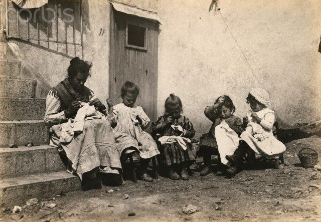 A mother sits with girls, making clothes for family members at war - 1916   #TuscanyAgriturismoGiratola
