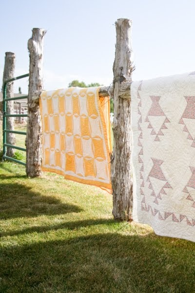 Vintage quilts spread over ugly fences.
