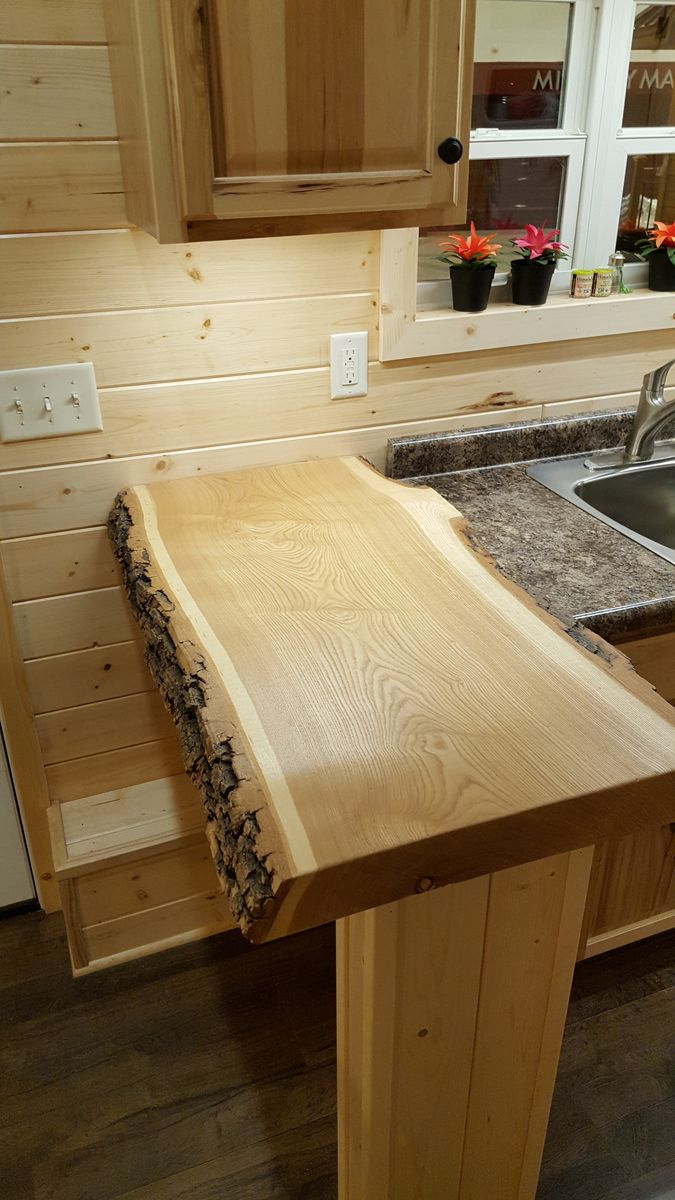 In the galley kitchen is a beautiful live edge bar height countertop, upper cabinets, gas range, and refrigerator.