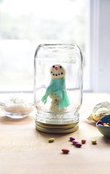 This snowman snow globe—inspired by an idea in Elise Strachan's new book, Sweet! Celebrations—is almost too cute to eat!  1. Melt 3.5 oz. white candy melts and place 1 Tbs. on the inside of a mason jar lid. 2. Set 1 coconut truffle (we used Raffaello brand) in the melted candy and refrigerate to set. Then place ¼ tsp. melted candy on the coconut truffle and glue a second one on top. Allow to set. 3. Use the same technique to attach a white chocolate truffle (we used Lindt's Lindor) ...