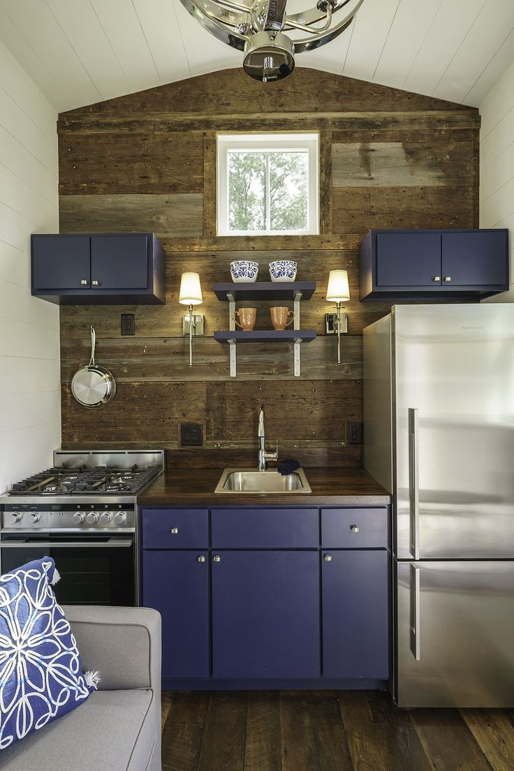 Kitchen with blue cabinets and stainless appliances in a tiny house.