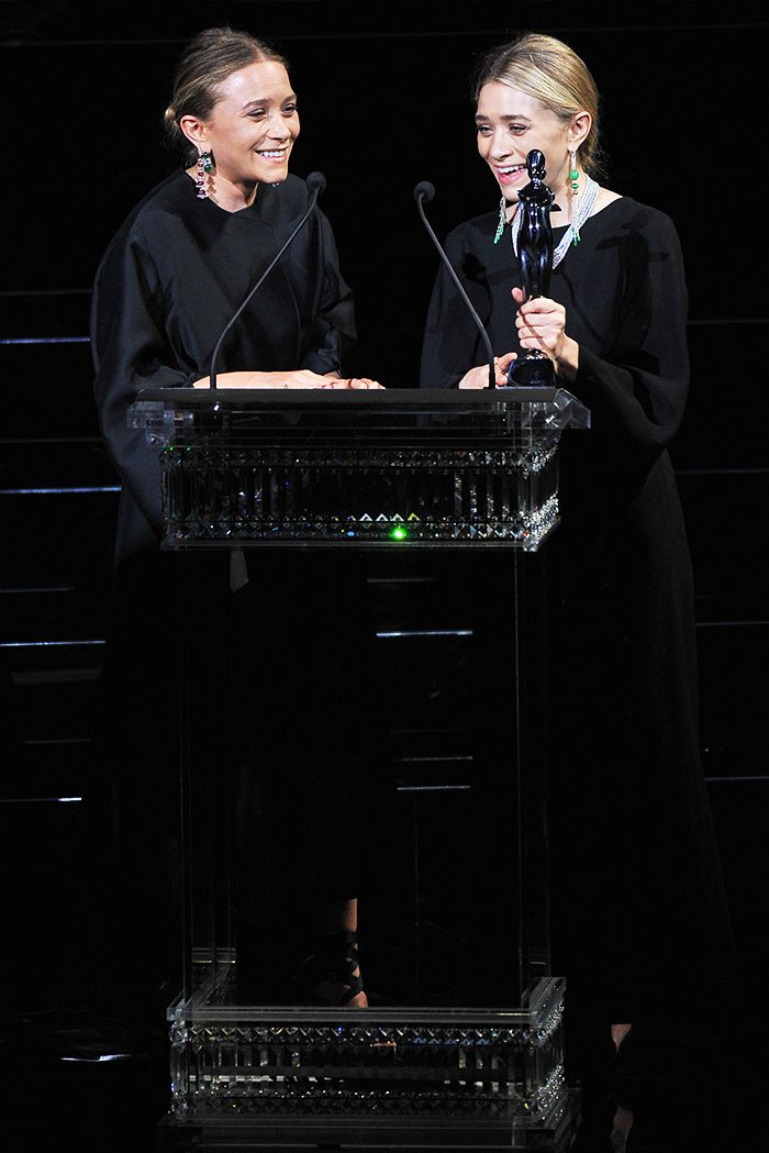 Mary-Kate and Ashley Olsen wear their signature all-black looks while accepting an award