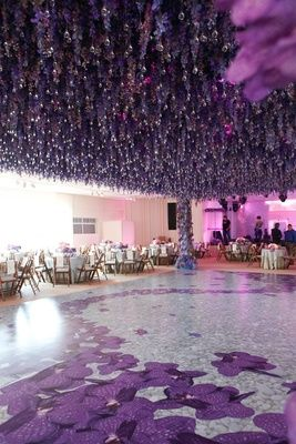 a structure made of pink and purple flowers purple flowers hanging crystals over floral dance floor
