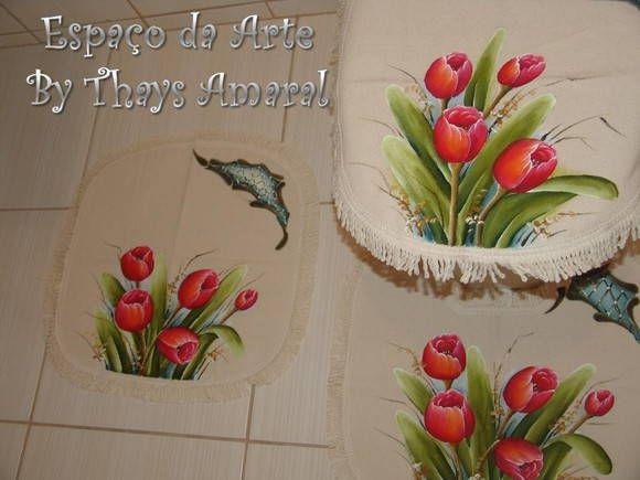 Deixe o seu banheiro um charme com esse jogo de banheiro pintado à mão! <br> <br>O kit é composto por 3 peças, sendo: 1 tapete (50x50), 1 tapete para vaso (45x50) e 1 tampa de vaso (44x48). <br> <br>As franjas dão um toque especial no acabamento. <br> <br>O tempo para produzir pode variar conforme o pedido . <br> <br>Valor do frete não incluso no preço.