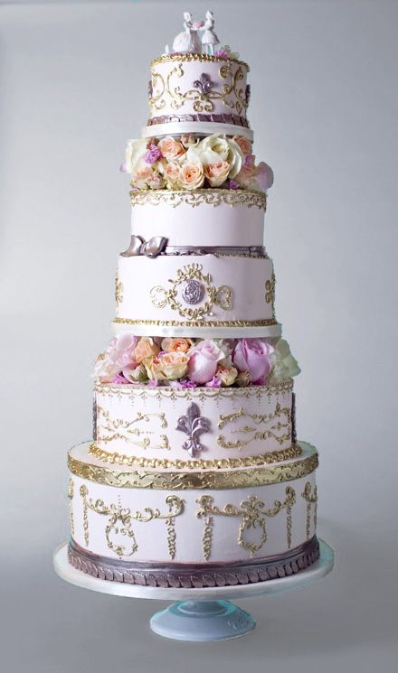 Classic, beautiful, ornate, delicate, elegant French inspired wedding cake featuring porcelain cake toper, fresh flowers and intricate piping in a palette of lavender, pink, peach, yellow, purple and gold. Won of the most amazing wedding cakes I have ever seen.