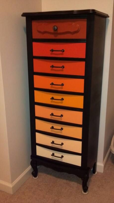 Repainted dresser with ombre orange drawers and new black hardware with copper finish