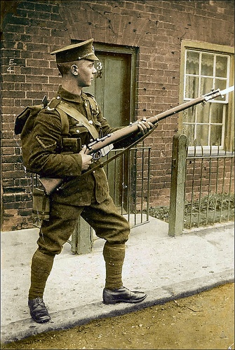 "Coloured postcard of a young British soldier stiking a ""on guard"" pose with a long Lee-Enfield MkI & 1888 pattern bayonet"