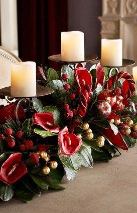 velas blancas, porta velas negro y flores rojas y blancas con hojas verdes.