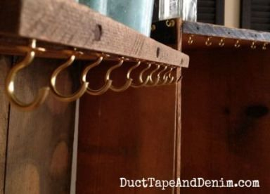 Close up of the cup hooks on my vintage crate necklace display. Vintage style boutique shop or flea market necklace display idea. Or use for jewelry organization at home. DIY | DuctTapeAndDenim.com