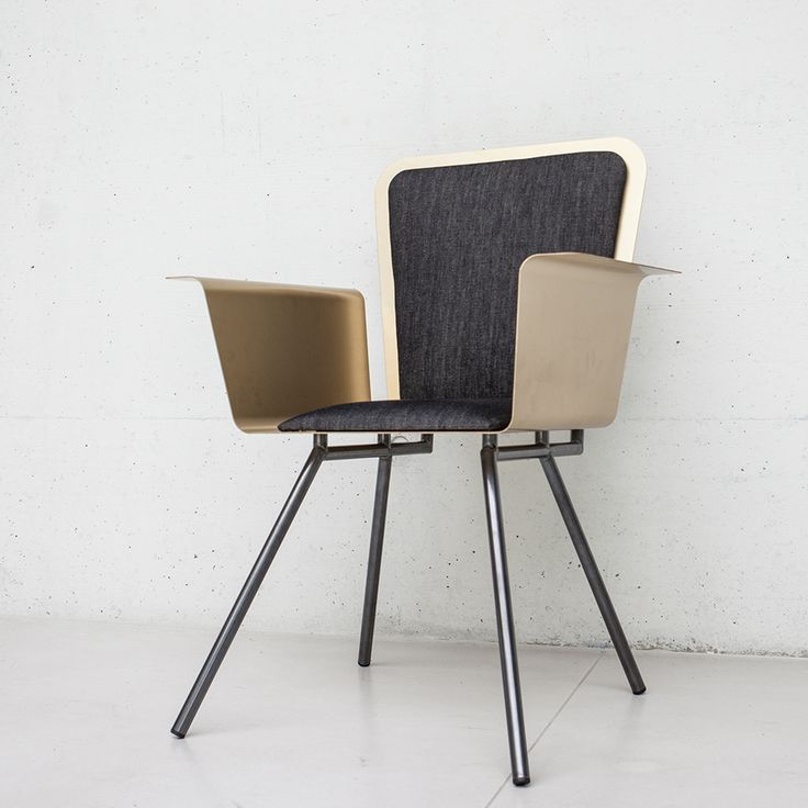 A Chair. This distinctive chair is lightweight, yet durable, supported on untreated steel legs. The glossy finish anodized aluminum shell – light gold in color – will help brighten any room.  The black denim cushions make this a chair both comfortable and chic. Perfect for reading or relaxing.
