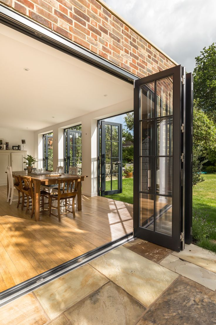 Single storey flat roof rear extension to detached home | French doors | industrial | hopper downpipe | side patio | folding doors | brick façade | level threshold | stone paving | wooden floor | Brighton architects