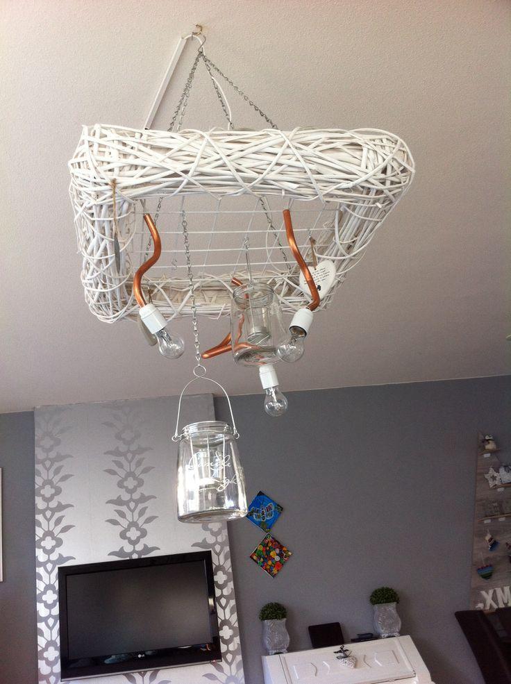 Rotan vierkant met betongaas. Hangende aan 4 kettingen. 3 koperen buisjes gebogen, fittingen eraan. Aan het betongaas kan je verschillende lichtjes hangen.